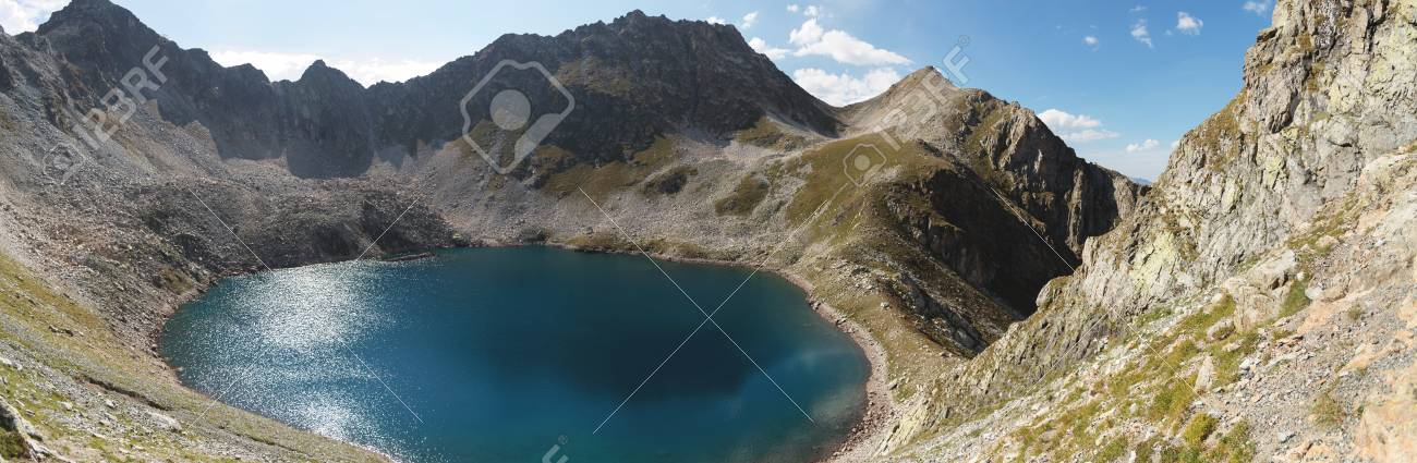 Landscape of highland lake high in the mountains of Dombai. Circus formed by a glacier with a deep lake and blue water - 113935498