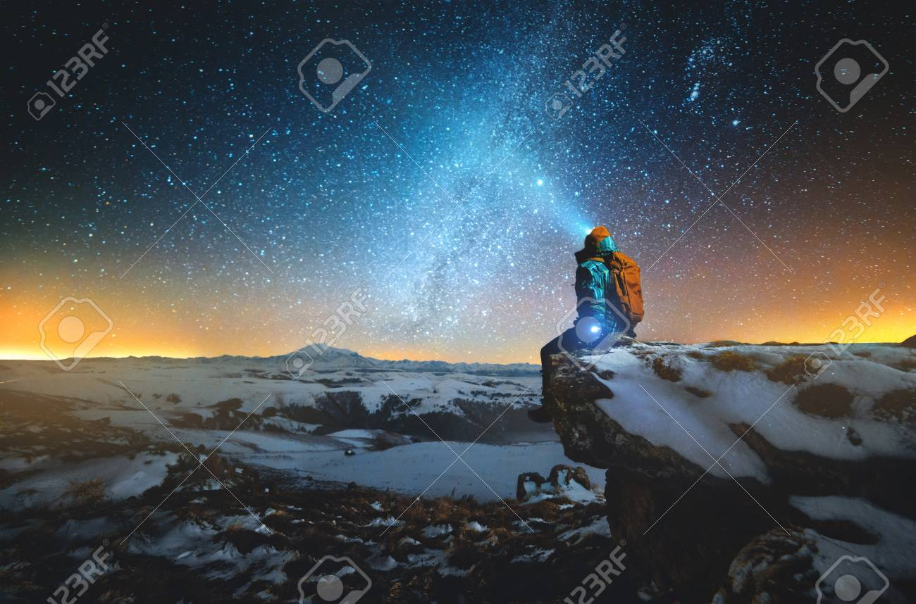 Night winter landscape a man with a backpack and a lantern on his head sits on a rock in the mountains in winter against the background of a mountain and a winter starry sky and the Milky Way - 120184877