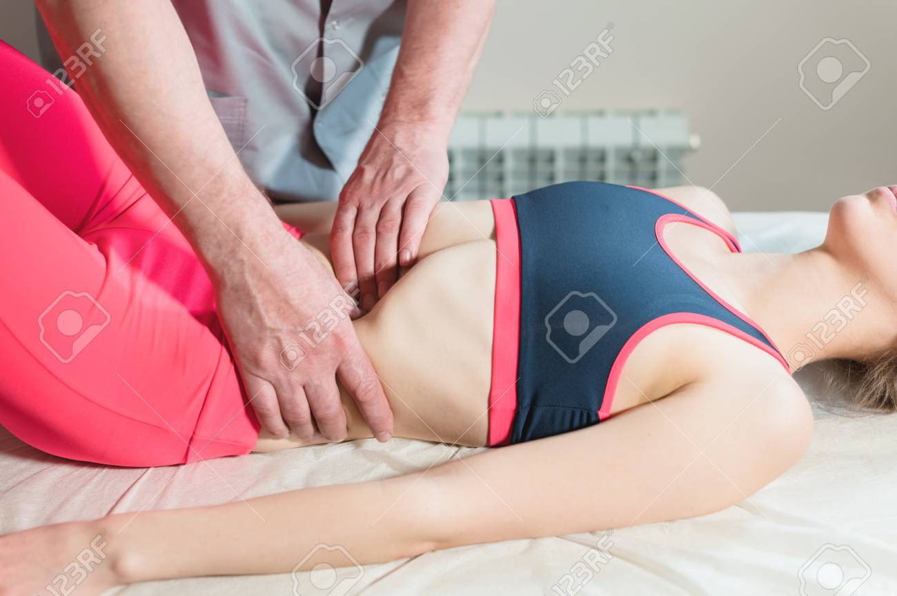 Male manual visceral therapist masseur treats a young female patient. Edit the internal organs and the elimination of adhesions in the stomach - 122547487