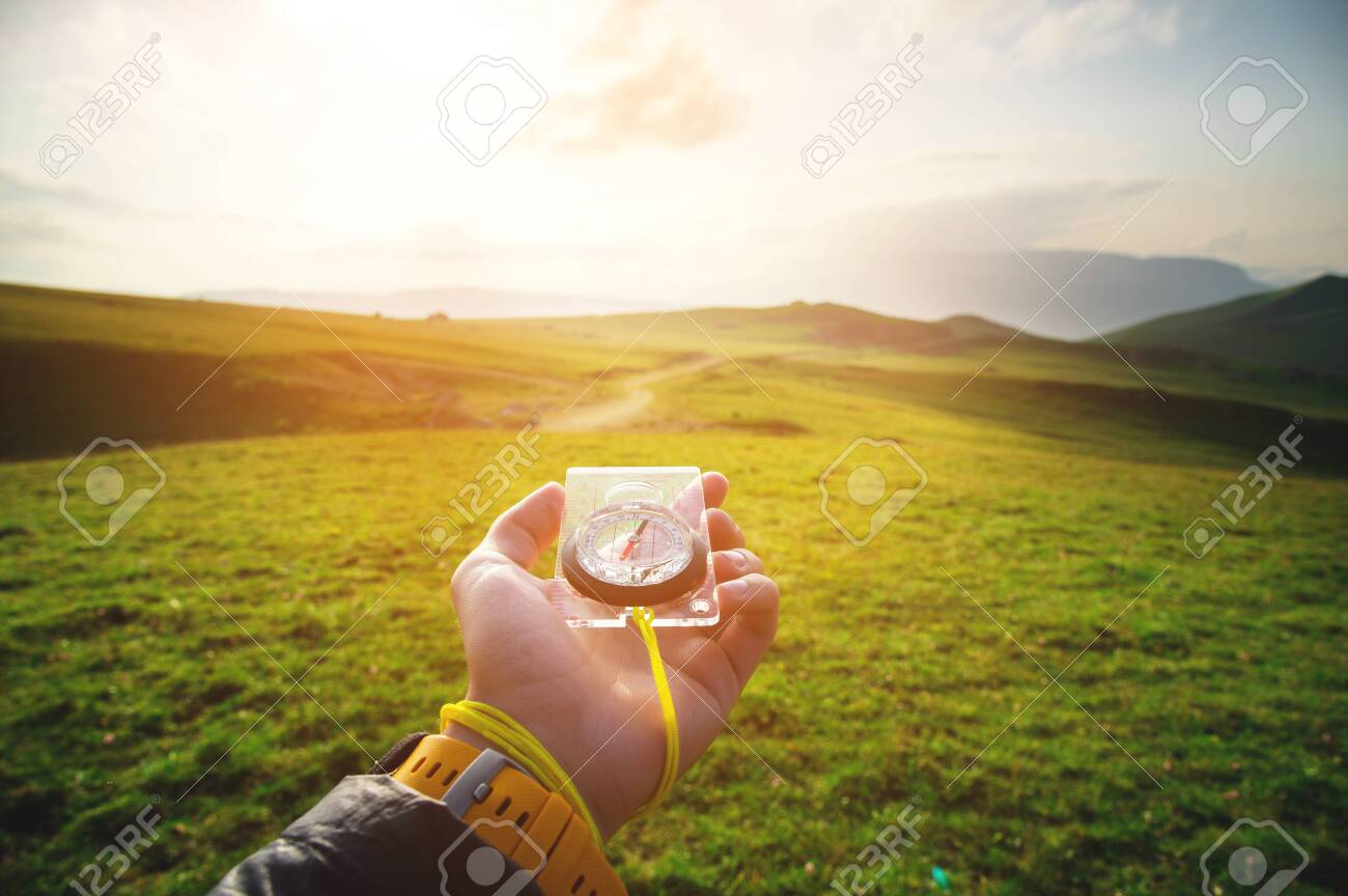 Male hand with a magnetic compass ea against the backdrop of a beautiful landscape at sunset. The concept of navigating the search for your own path and orientation to the cardinal points - 129415459