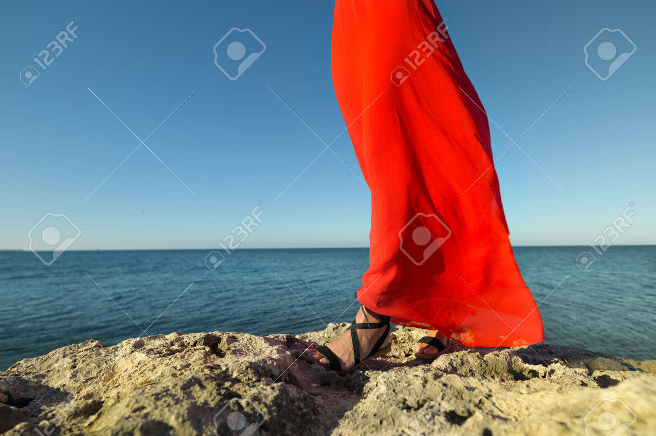 Lovely romantic caucasian young woman in red dress and straw hat against the background of the sea horizon in windy weather - 173333054