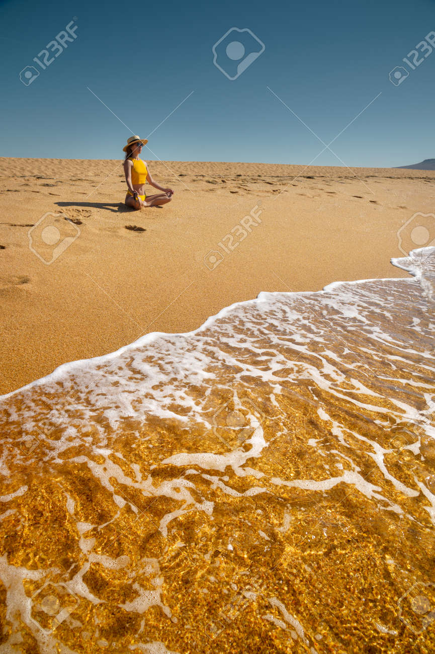 Young caucasian woman sits in lotus position on a golden beach by the ocean. Girl in a hat on the seashore meditates - 173333056