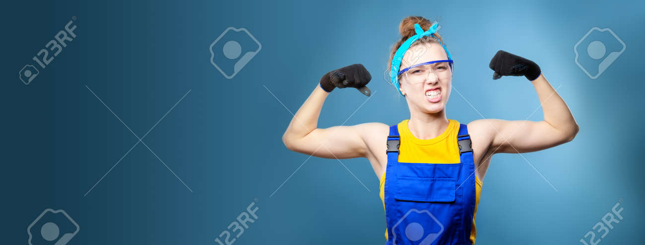 Panoramic shot. beautiful caucasian female repairman with blue eyes in uniform shows arm muscles, proudly smiles and makes a strong grimace. Studio shot on light blue background - 173333057