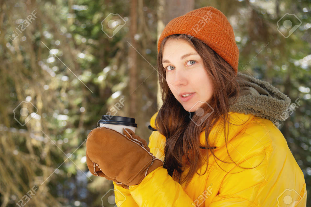 Attractive Caucasian positive young woman in winter clothes in a hat with mittens and a down jacket stands in a coniferous winter forest with a paper cup of coffee or tea. - 173333061