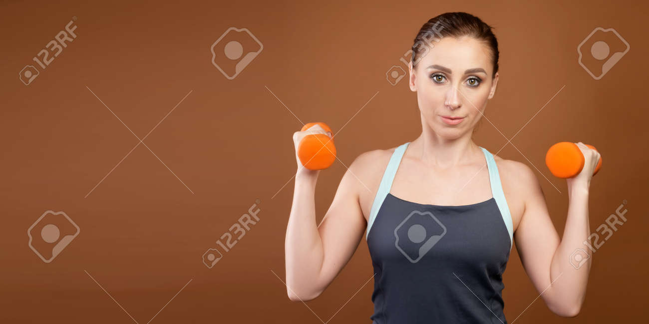 Panoramic shot of an athletic caucasian woman with dumbbells in her hands. Stands on a brown background with dumbbells in his hands and looks at the camera - 173333013
