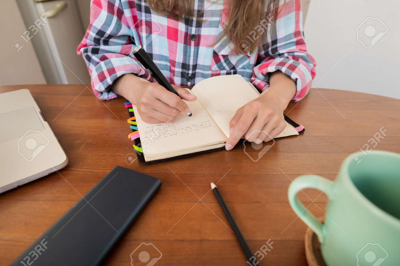 Young woman sitting at the kitchen table makes notes in a notebook. Home Office. Caucasian girl being homeschooled - 173333016