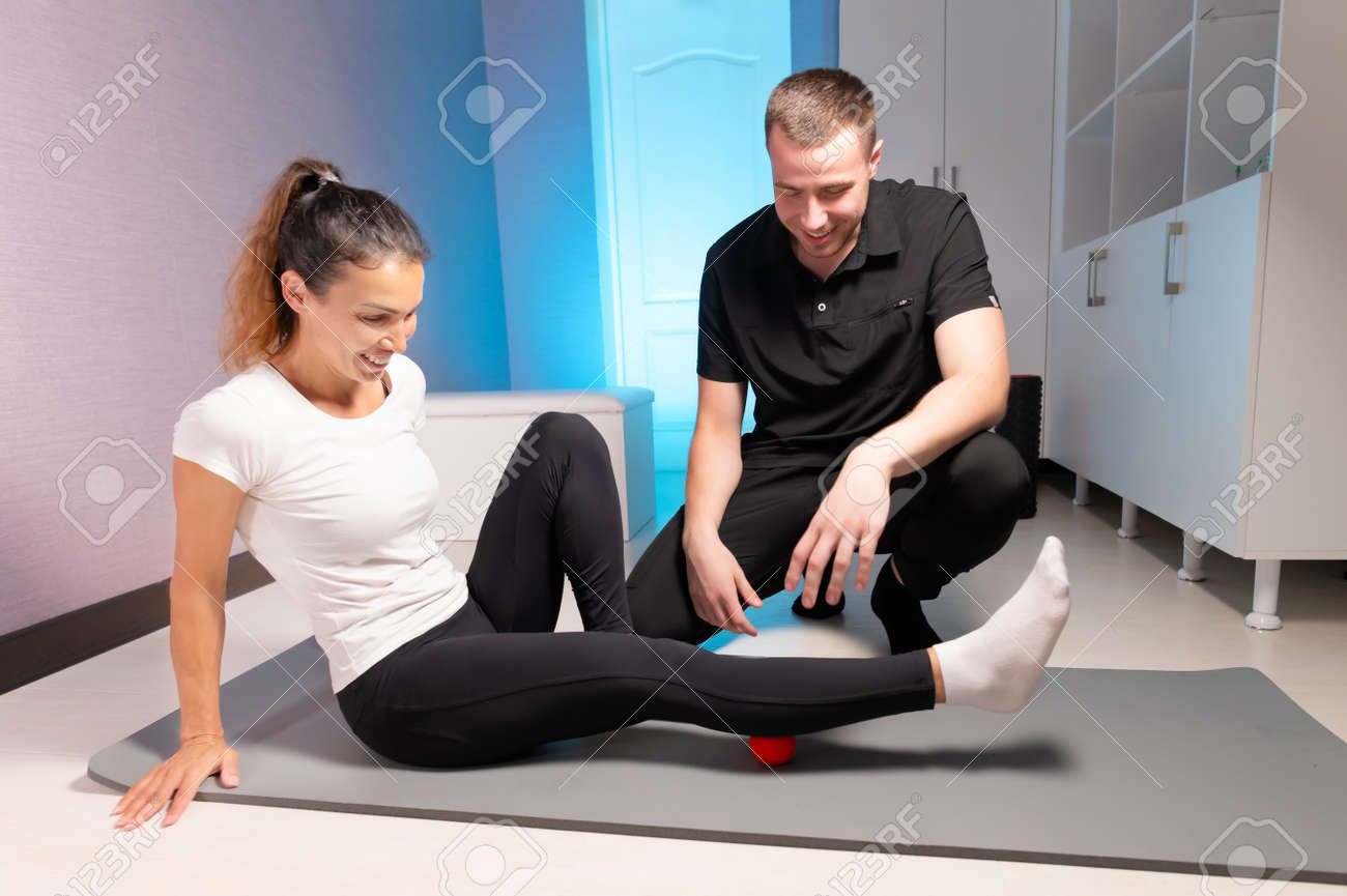Young caucasian male masseur showing and controlling myofascial massage of the fascia of the legs to a female client. Self-massage training using a massage ball - 173255780
