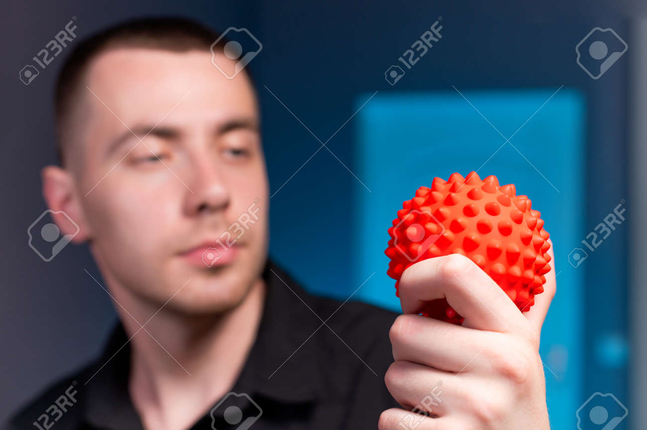 Portrait of a professional young caucasian male masseur in a dark uniform holding a massage ball in his hand for self-massage myofasceal - 173333020