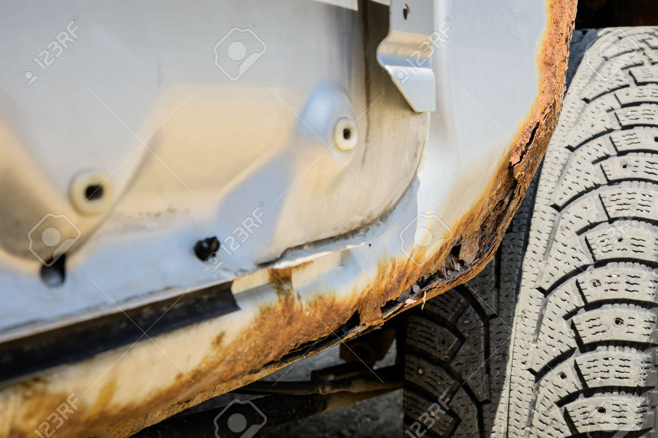 Rusty part of the car body with through-out corrosion. Background for cars requiring body repair - 173452019