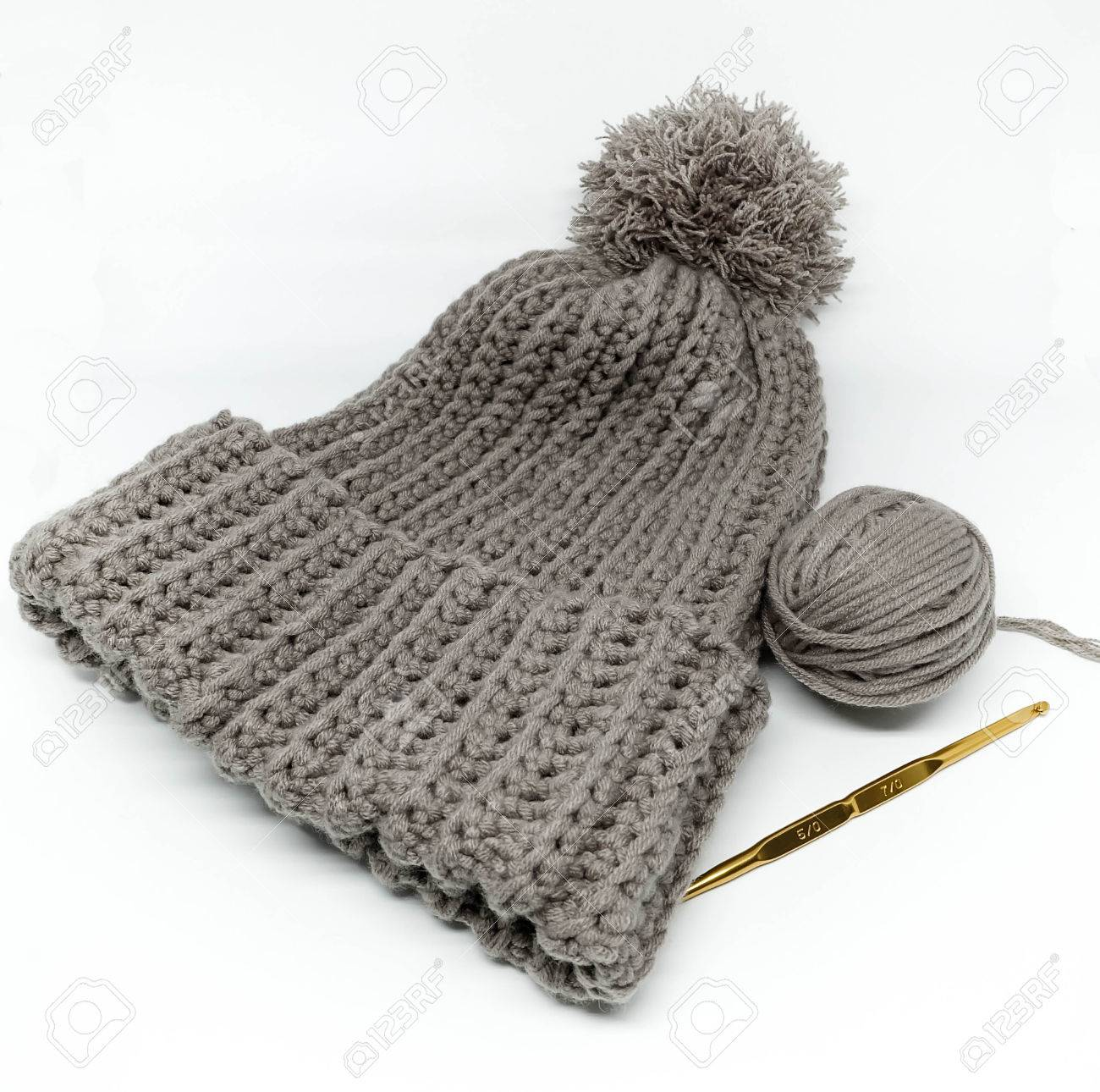 6e55d658 Gray Crochet Hat, Yarn Ball And Golden Needle Stock Photo, Picture ...