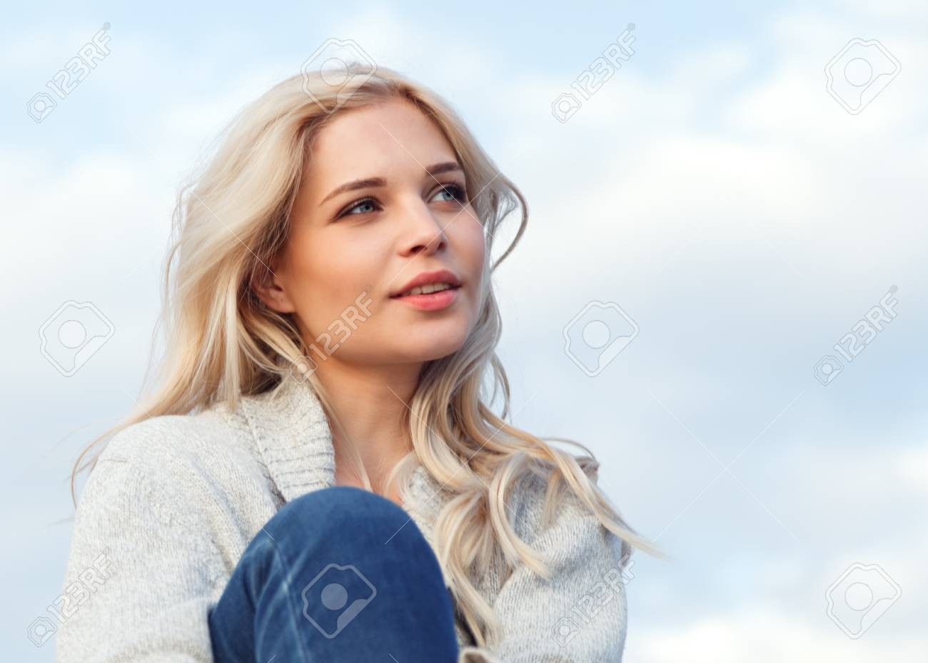 Beautiful happy blonde in a gray sweater and jeans smiling against the blue sky. Travel, leisure, tourism concept. - 125840183