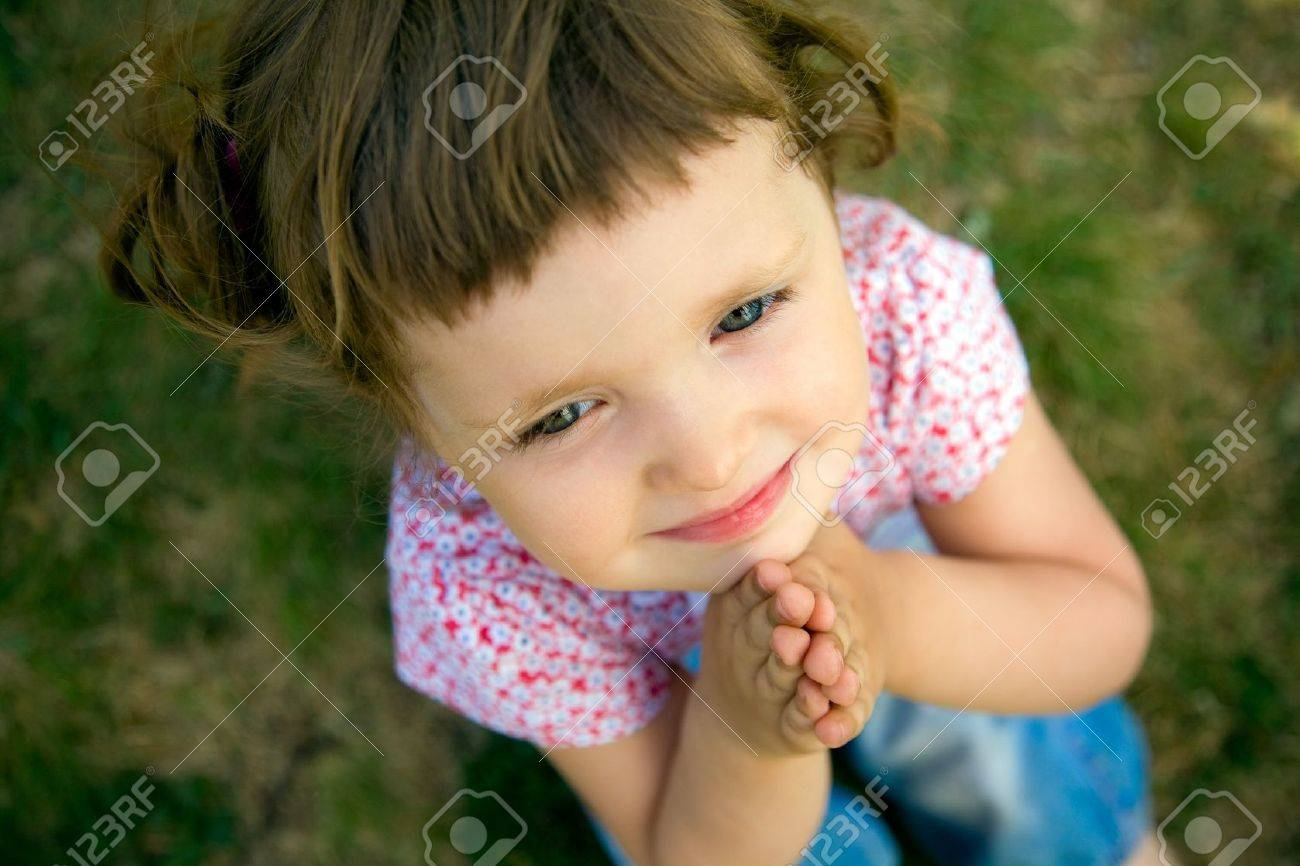 pretty young girl praying with her hands held together Stock Photo - 9131588