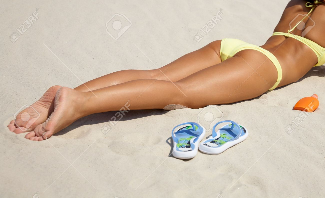 unrecognizable beautiful young woman in bikini lying and sunning on the beach under the bright sun Stock Photo - 9131720