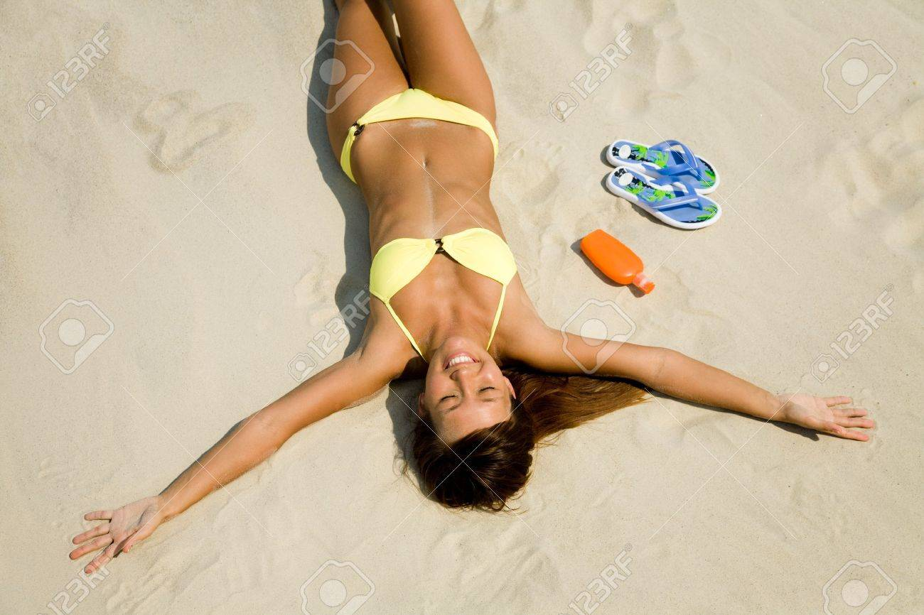 beautiful young woman in bikini lying and sunning on the beach under the bright sun Stock Photo - 9132050