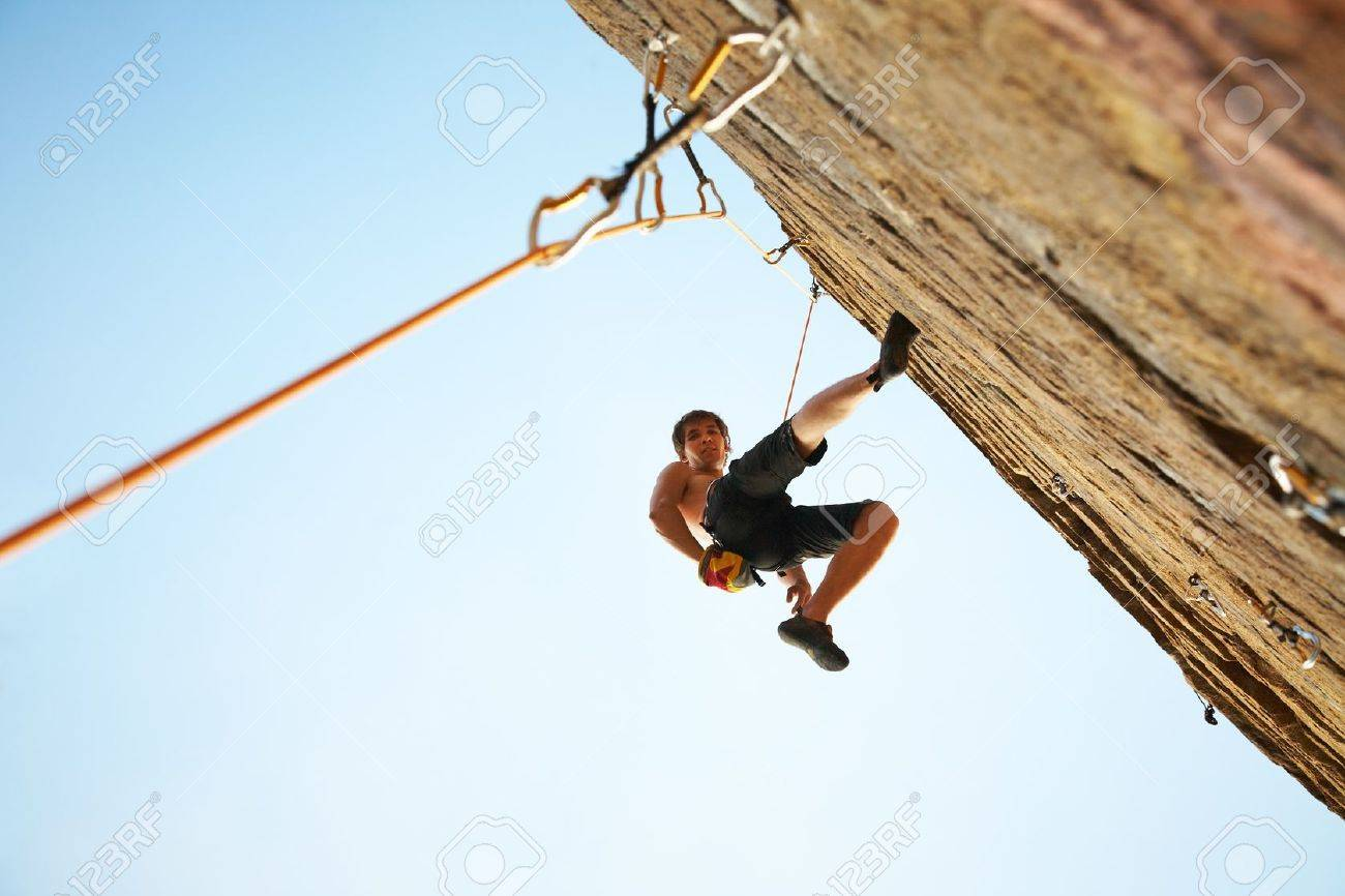 silhouette of rock climber climbing an overhanging cliff against the blue sky Stock Photo - 10430521