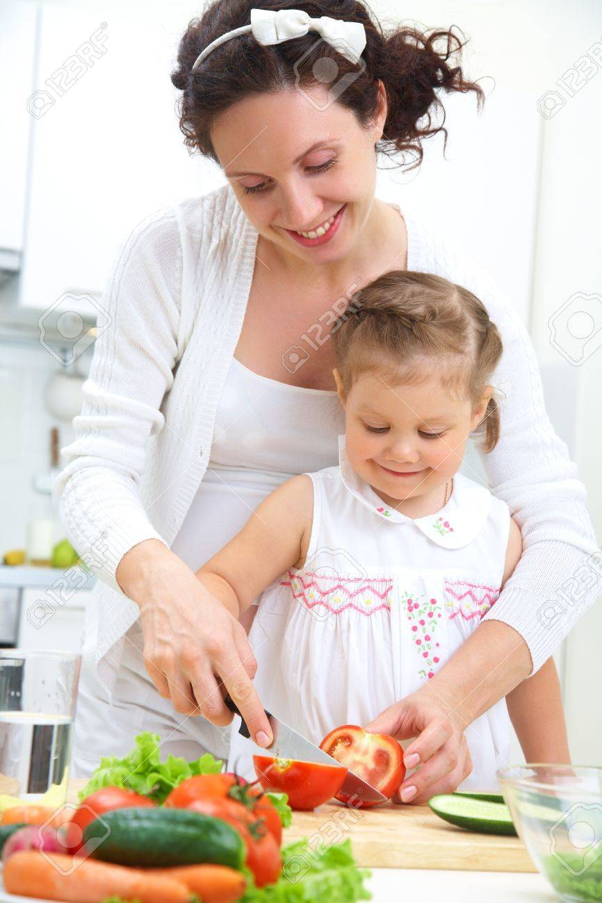 Mother and daughter in kitchen making a salad Stock Photo - 10511722