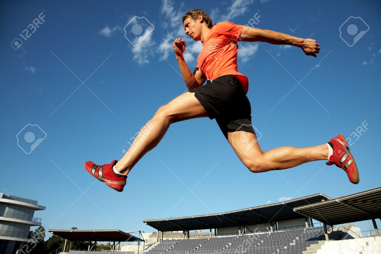 young muscular athlete is running  at the stadium background of blue sky Stock Photo - 10575692