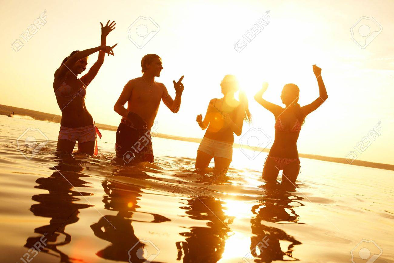 group of happy young people dancing and spraying at the beach on  beautiful summer sunset Stock Photo - 10588611
