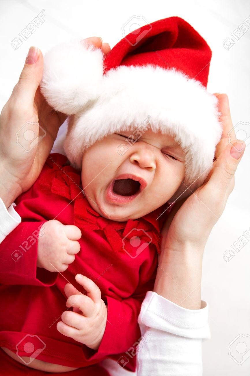 cute baby in santa hat sleeping in mother s hands stock photo