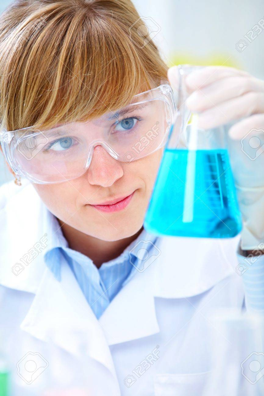 Young blond woman looking into a conical flask of blue coloured solution (liquid). Stock Photo - 11334186
