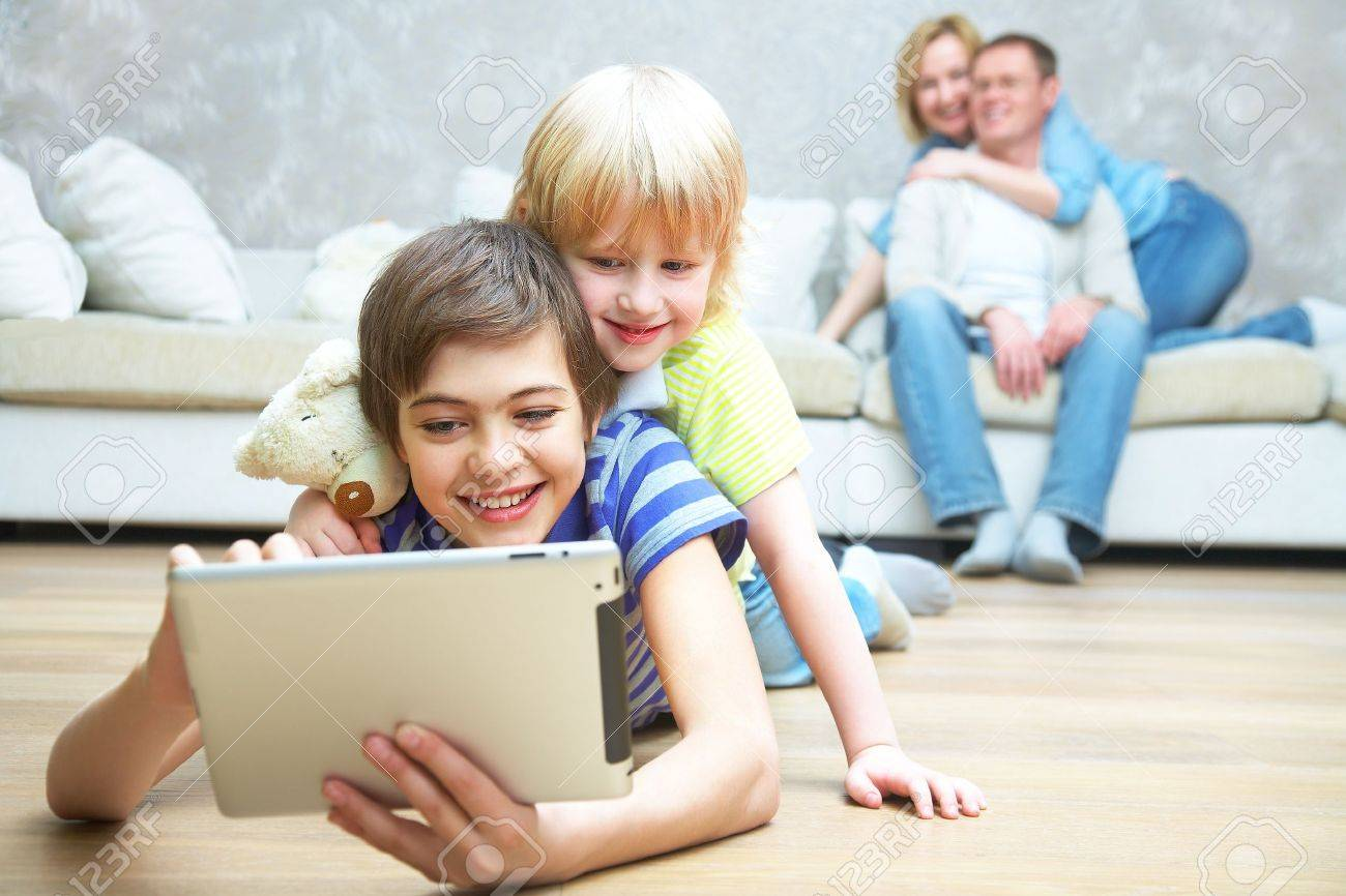 Two children playing with laptop on floor.  Parents sitting on sofa. Selective focus to children. Stock Photo - 15896971
