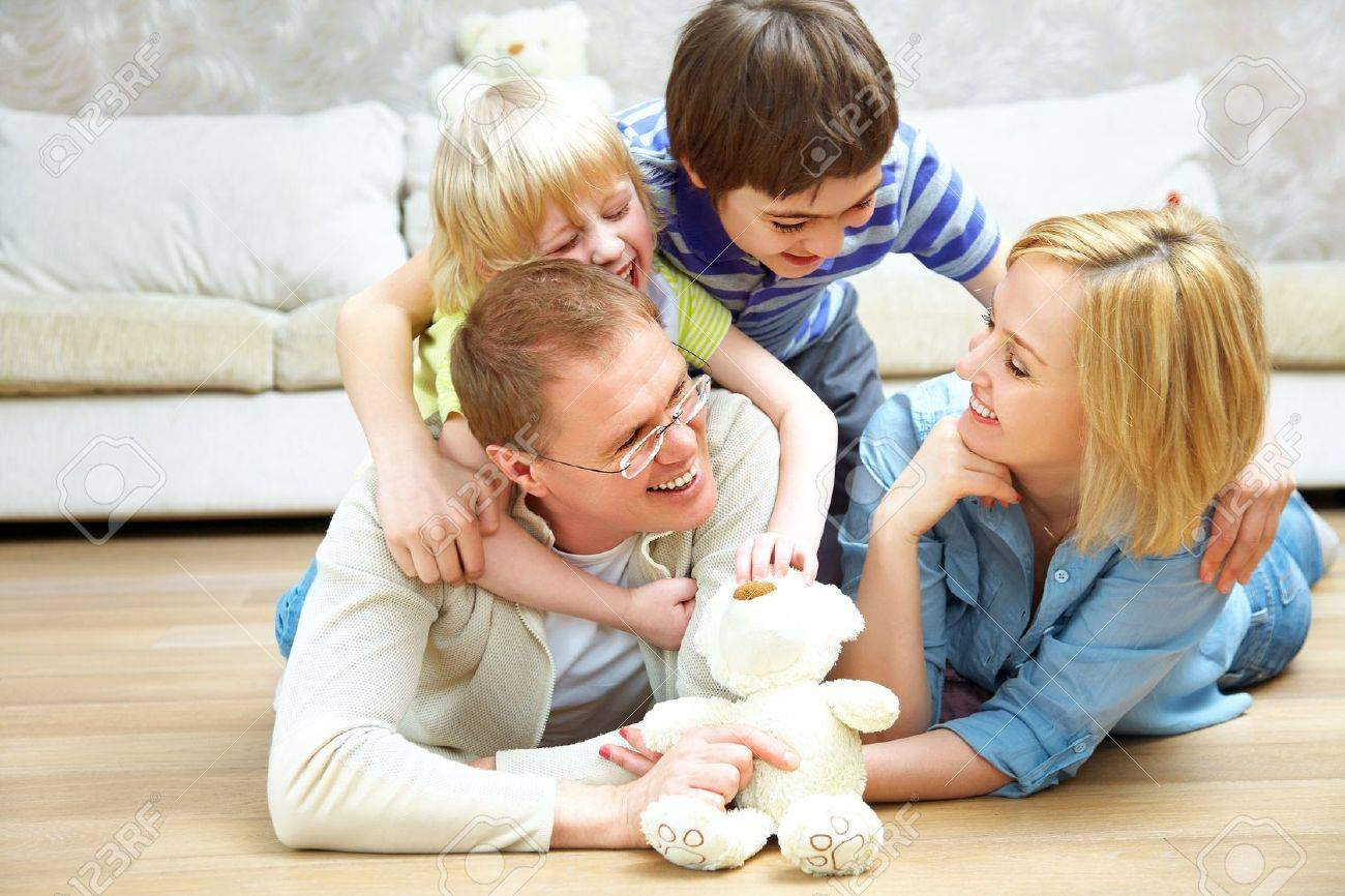 Portrait of family lying on floor living room and smiling to camera Stock Photo - 15871528