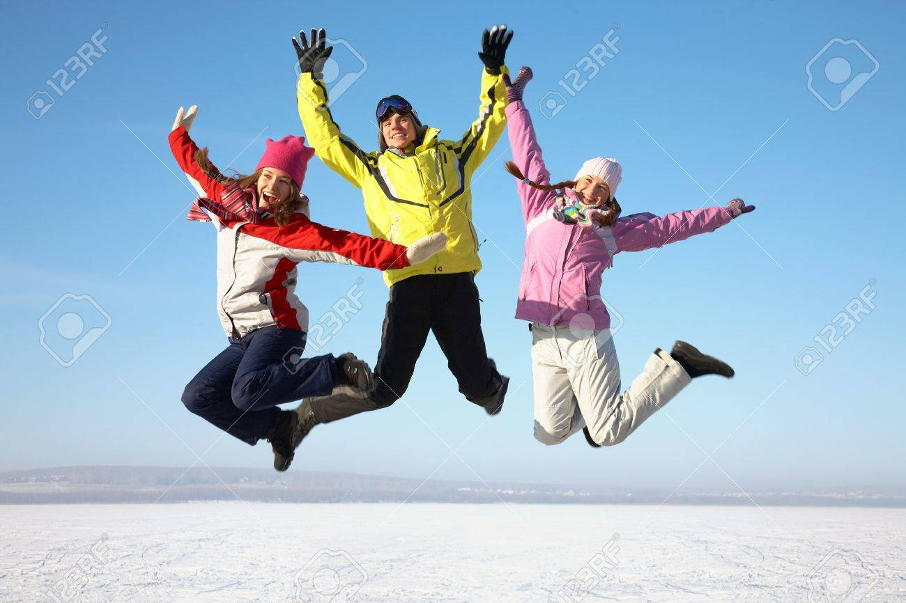 three friends joyfully jump into the sky over snow drifts in the winter Stock Photo - 16035891