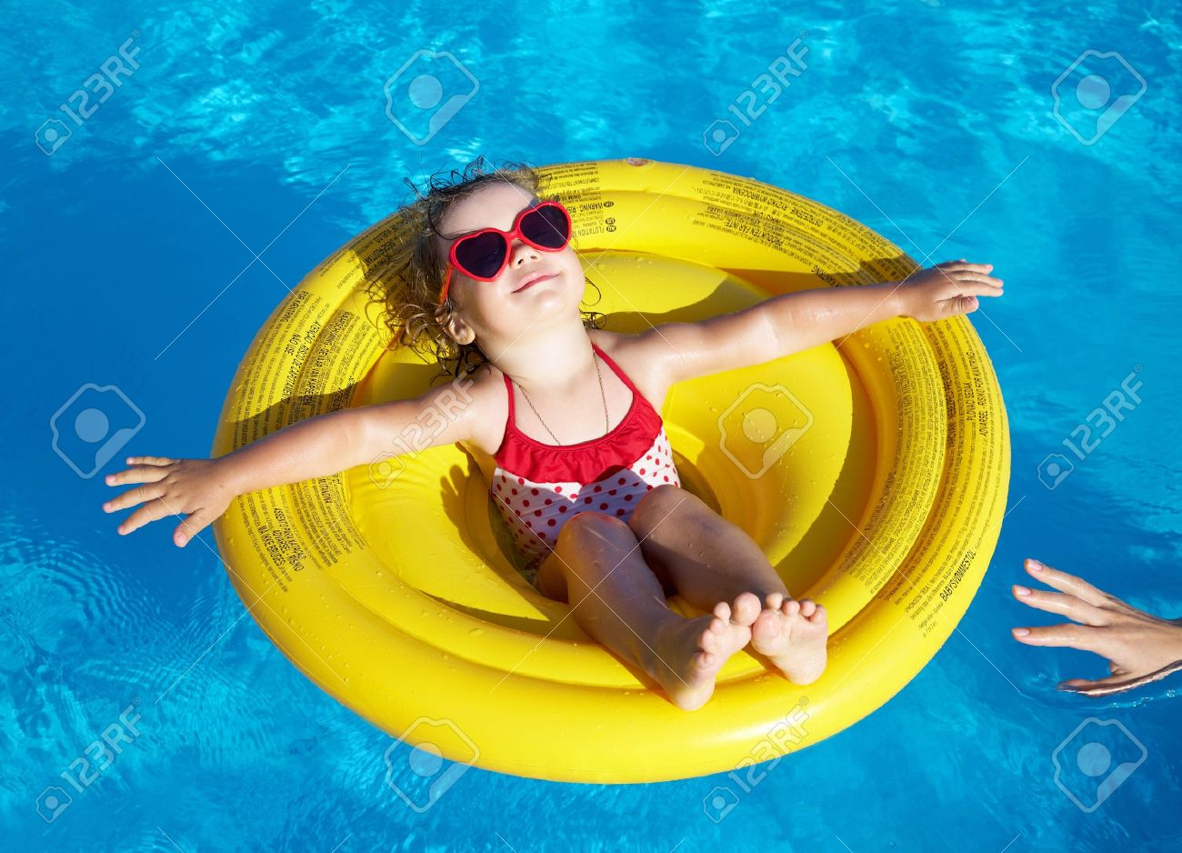 Funny little girl swims in a pool in an yellow life preserver - 21606849