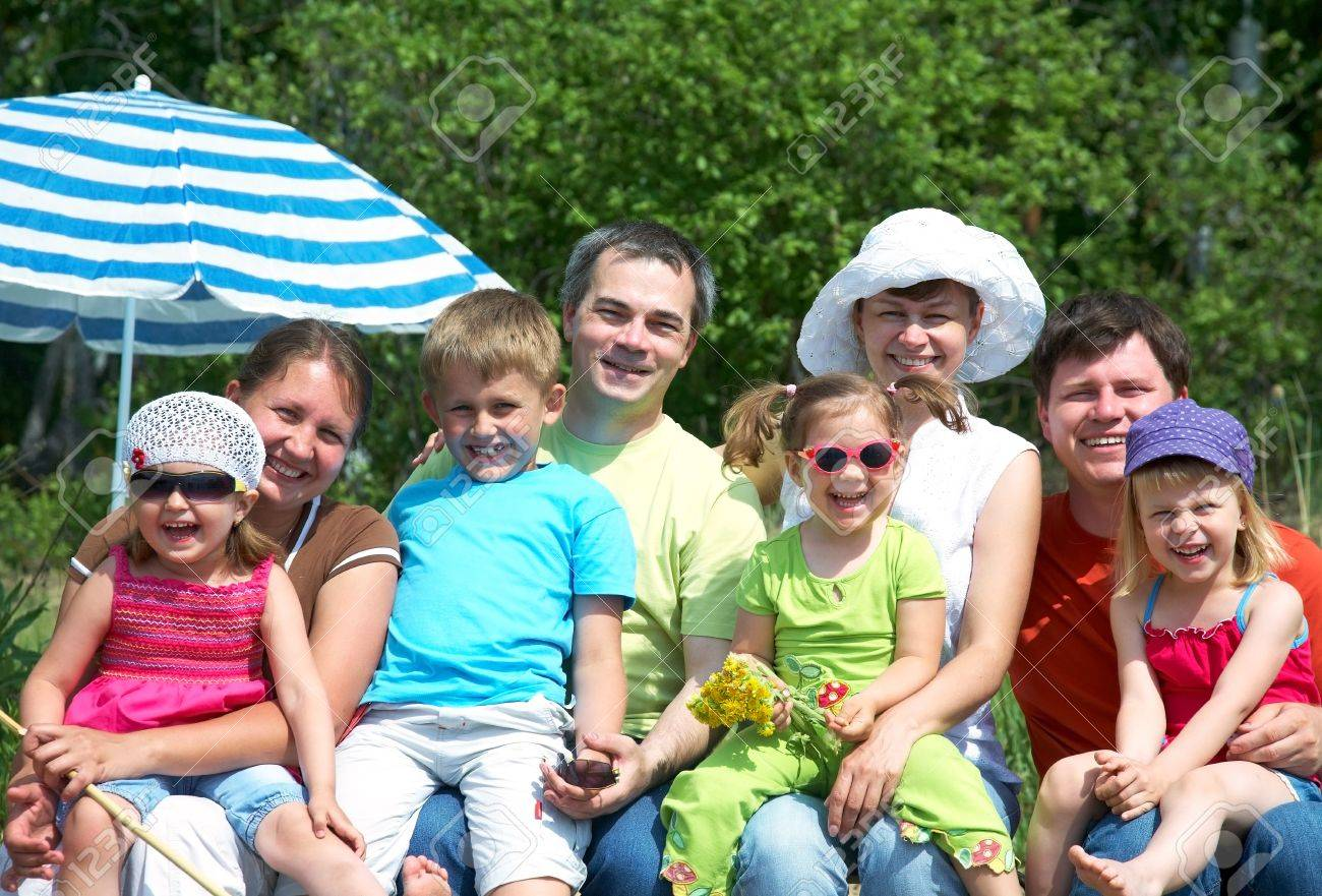 Portrait of big family  with their little daughter under beach umbrella Stock Photo - 21505129