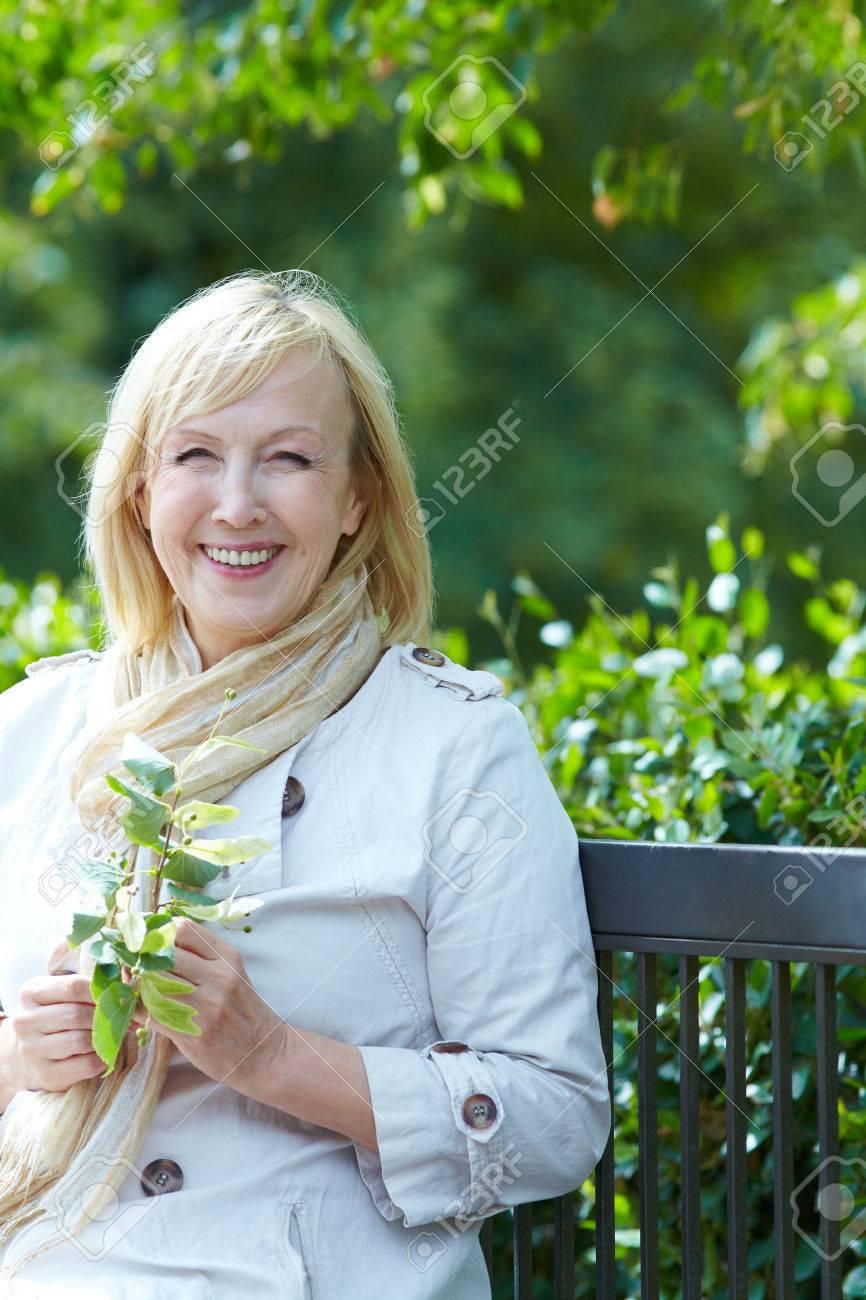 Happy  senior woman  sitting on a park bench Stock Photo - 22360708