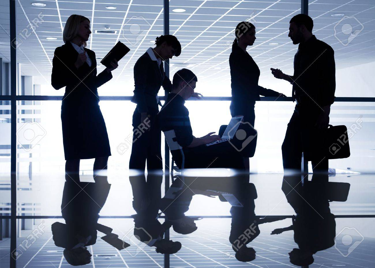 Several silhouettes of businesspeople interacting  background business centre Stock Photo - 27439092
