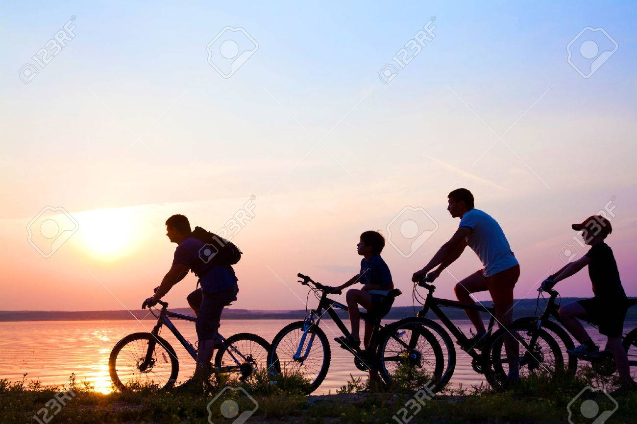 family on bicycles admiring the sunset on the lake. silhouette Stock Photo - 27439625
