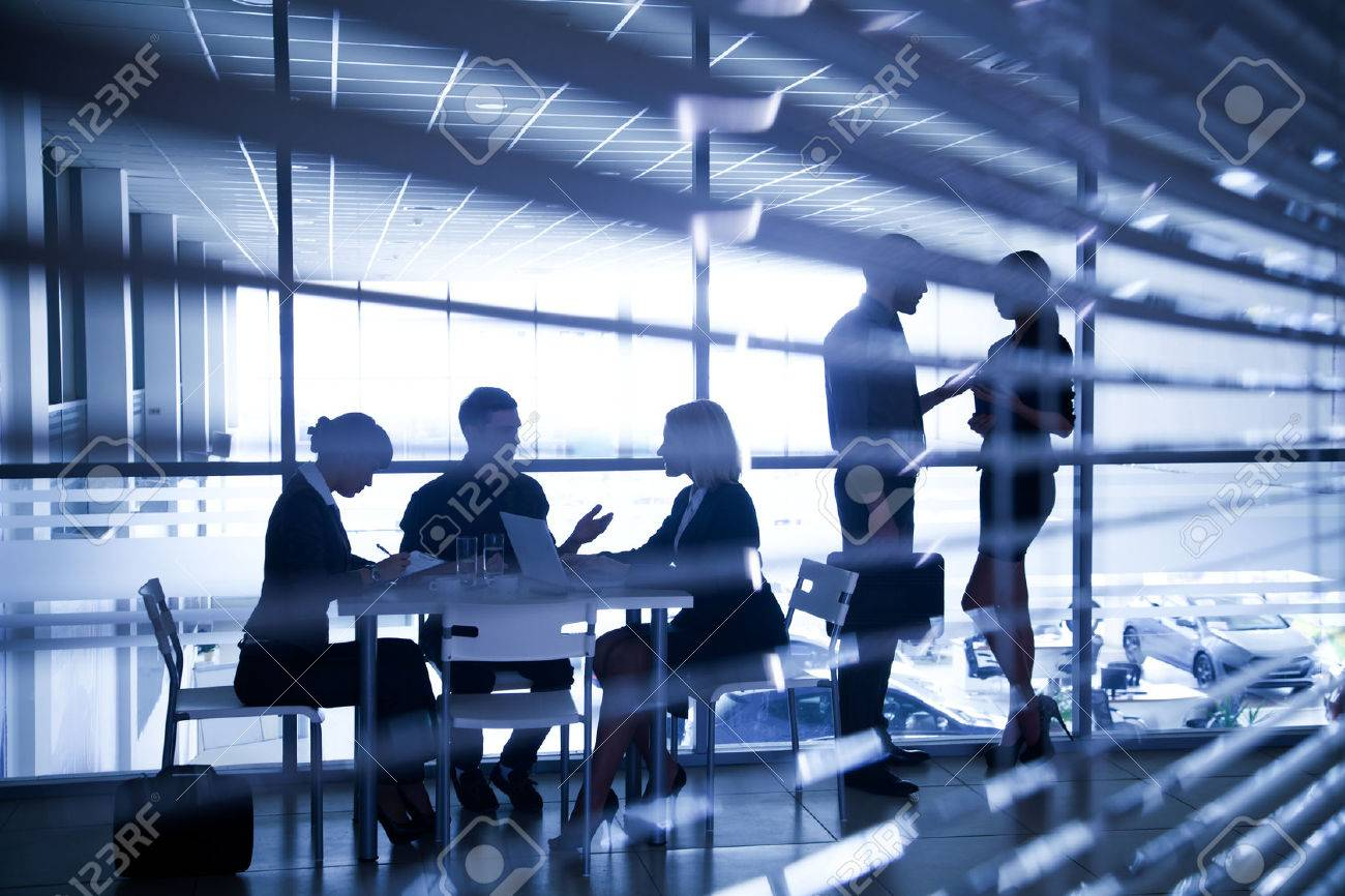 Several silhouettes of businesspeople interacting  background business centre Stock Photo - 27439683