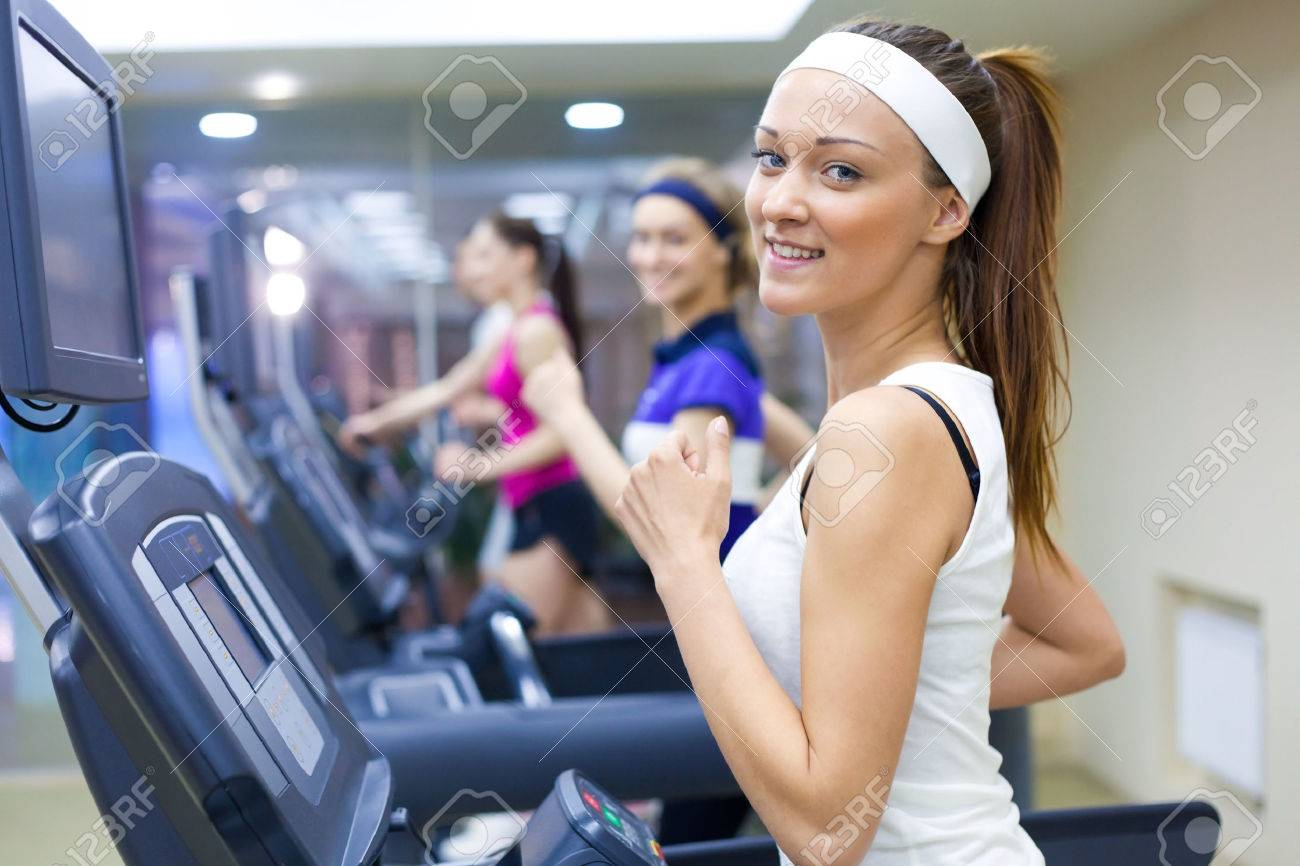 group of young people running on treadmill in gym Stock Photo - 27439750