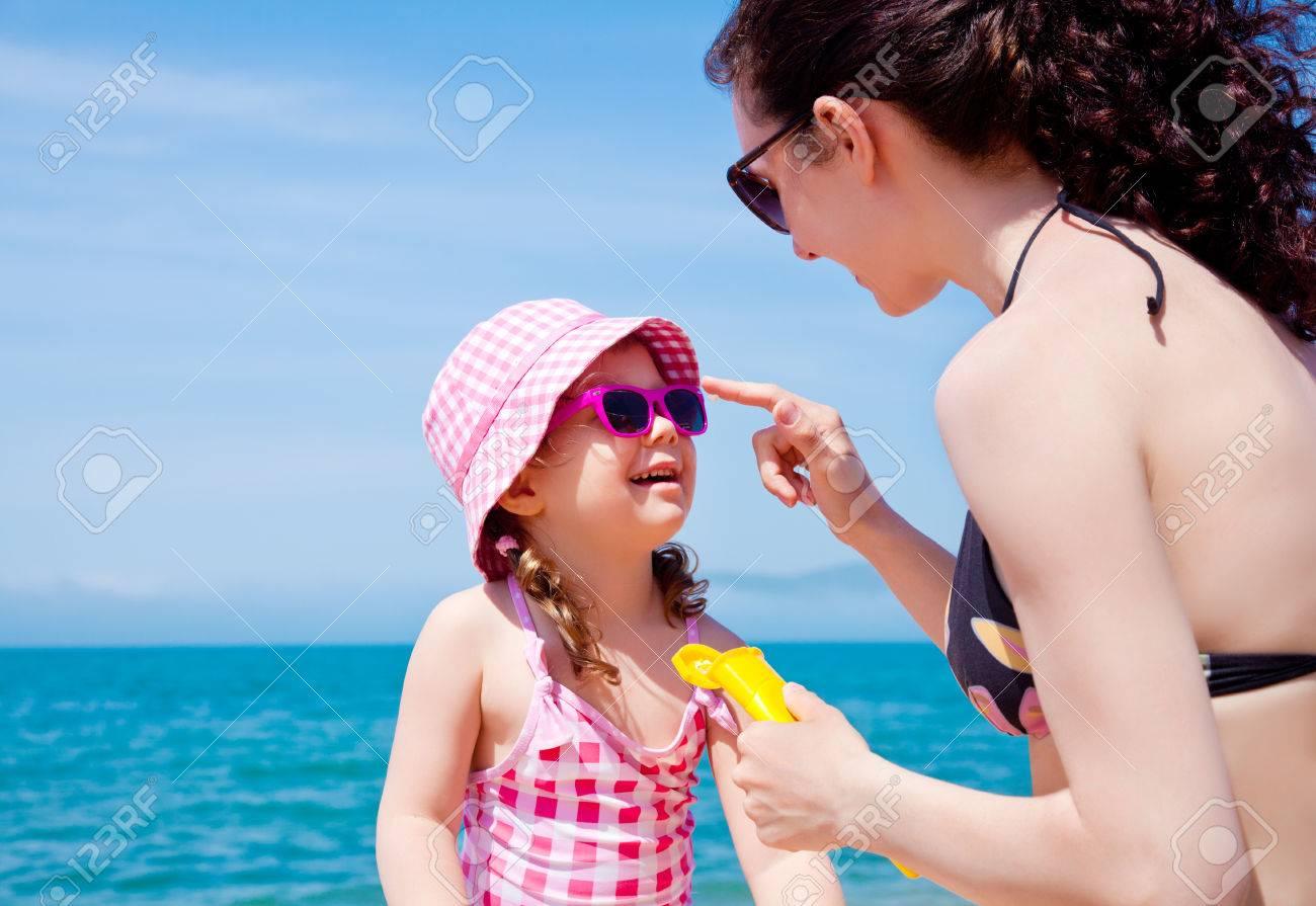 Mom anoints protective cream face a little girl on the beach Stock Photo - 27439776