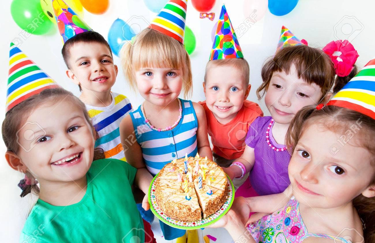 groupe d'enfants à la fête d'anniversaire avec un gâteau Banque d'images - 53291908