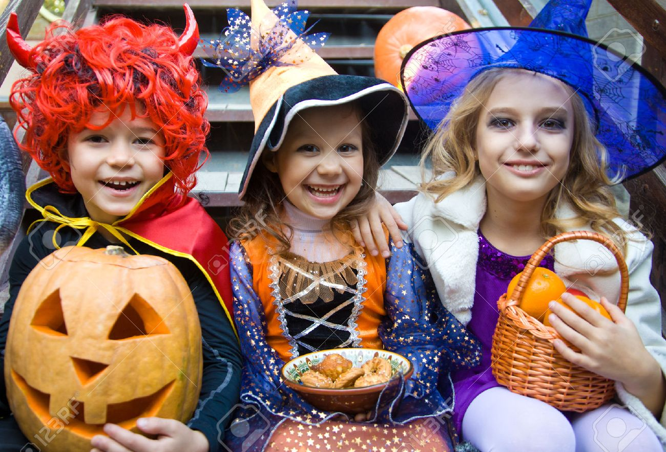 children in halloween costumes with pumpkin fooled on holiday Stock Photo - 31928406