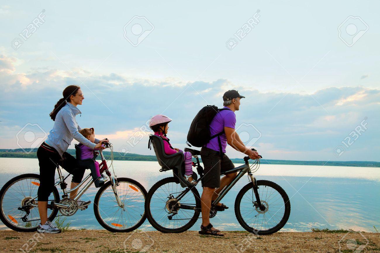 Young family with two kids go for a cycle ride on the beach at background sunset Stock Photo - 33898263