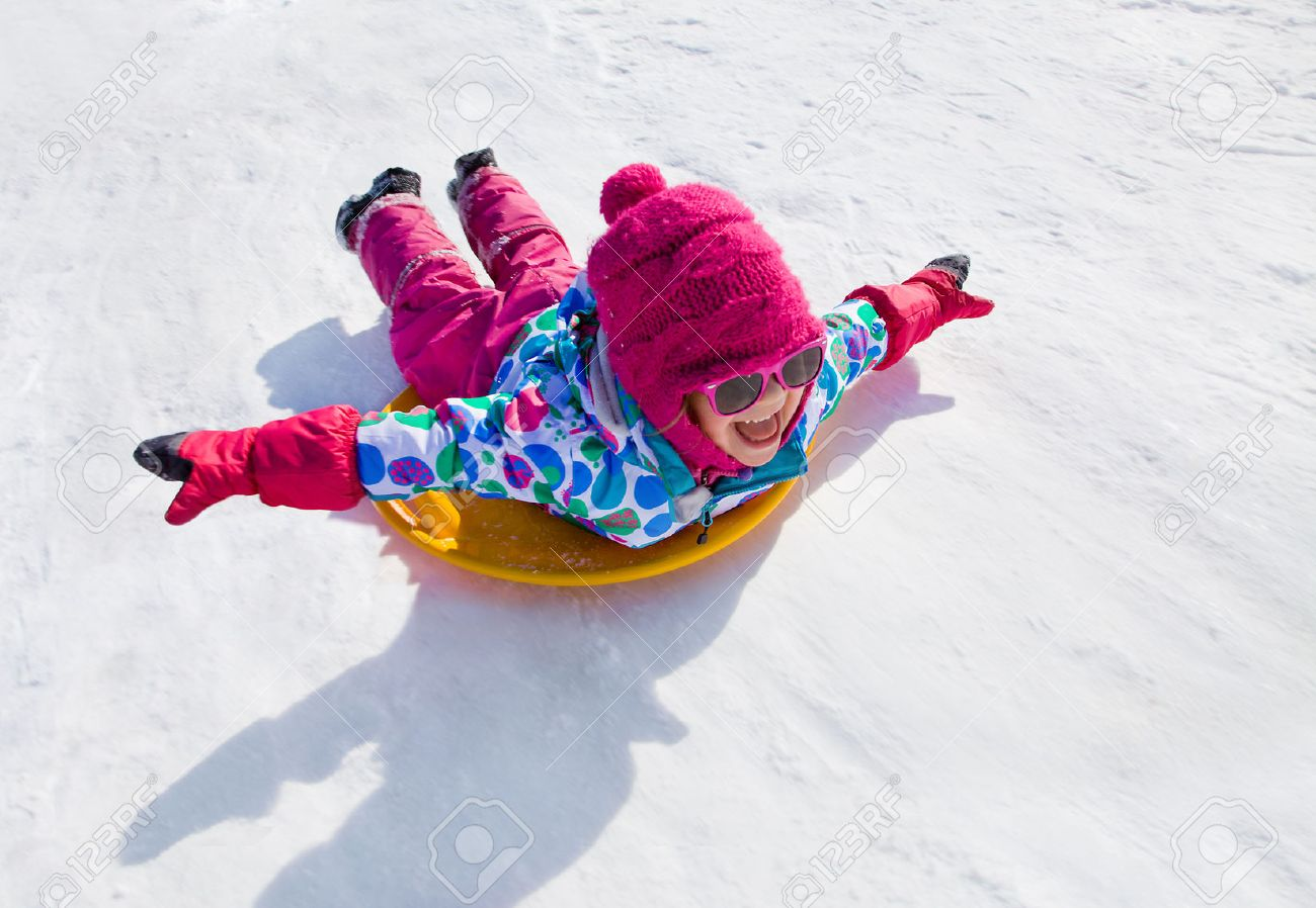 little girl riding on snow slides in winter time Stock Photo - 34267738