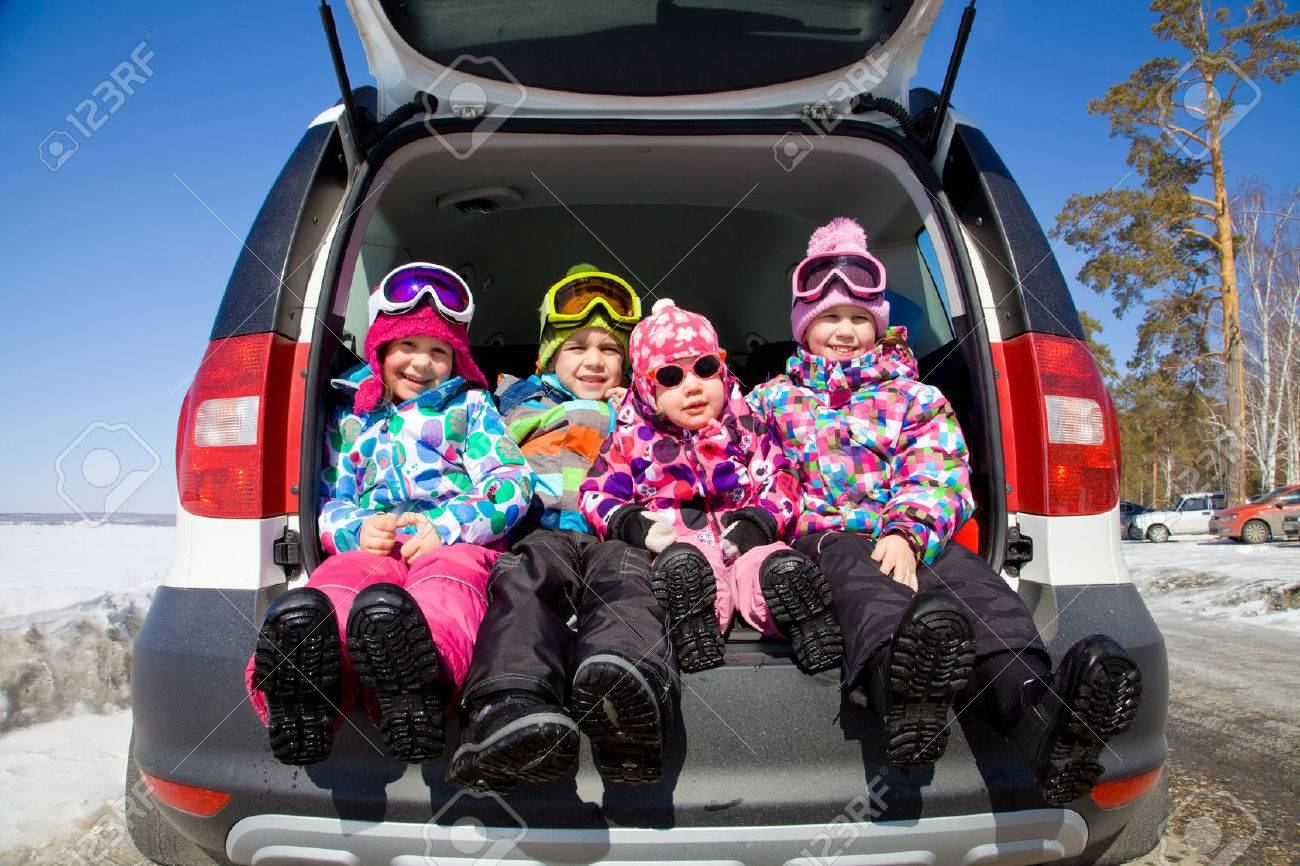 group of kids in winter clothes sitting in the trunk of a car Stock Photo - 33898274