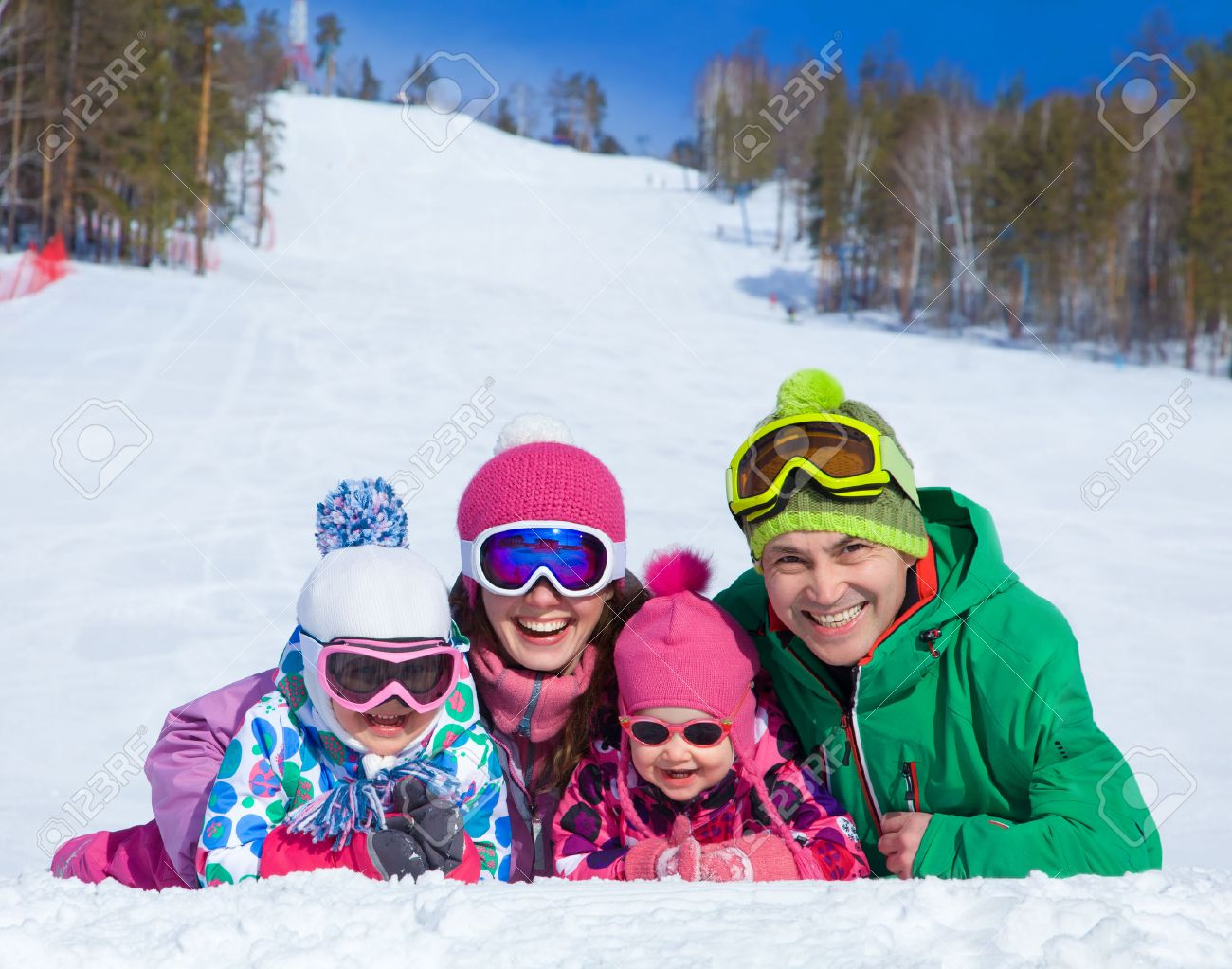 happy family in winter clothes lie on the snow at ski resort Stock Photo - 33977608
