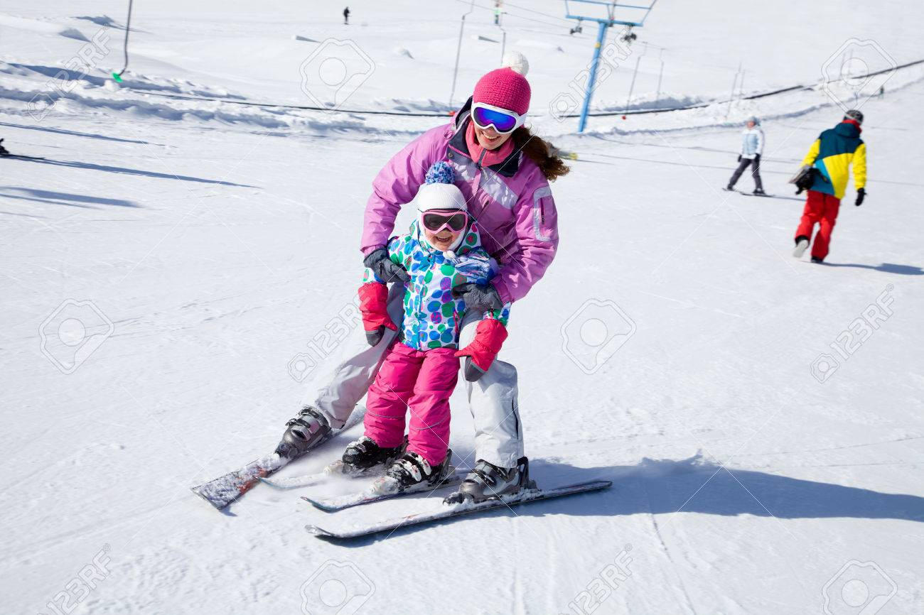 Female instructors teach a child skiing on winter resort Stock Photo - 33977787