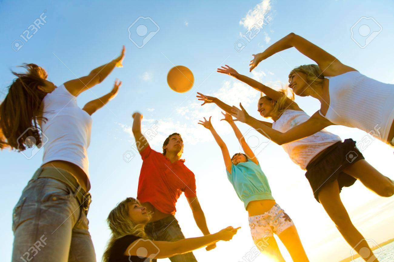 groupe de jeunes à jouer au volleyball sur la plage de coucher du soleil Banque d'images - 36651770