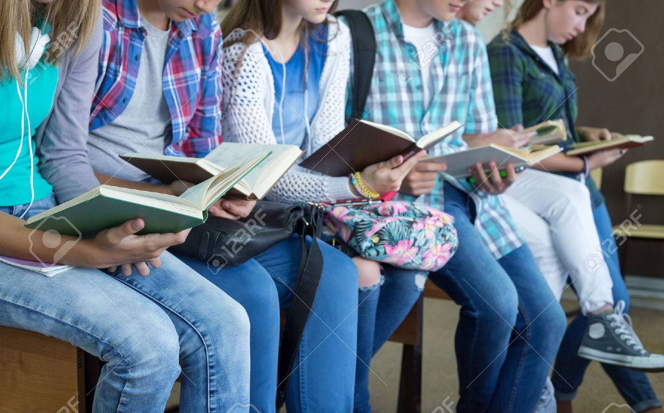 Teenage students in library reading books Stock Photo - 45903113