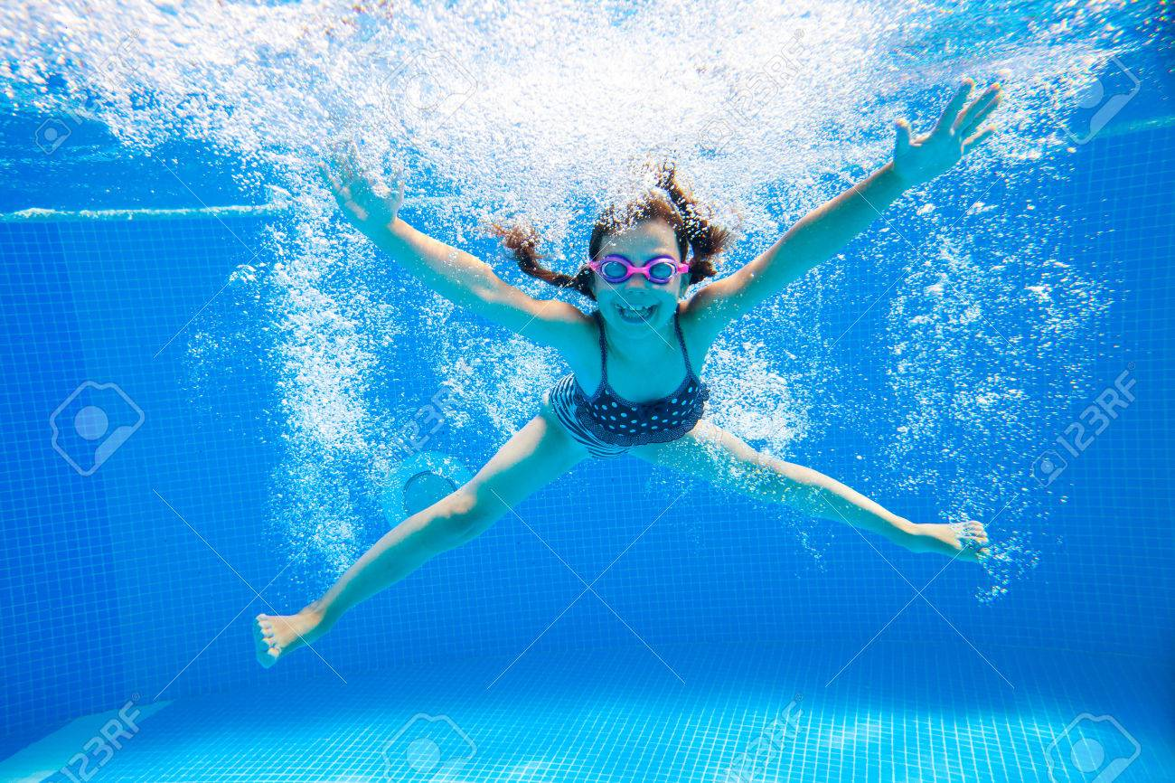 little girl creates bubbles under water in the pool Stock Photo - 45903151
