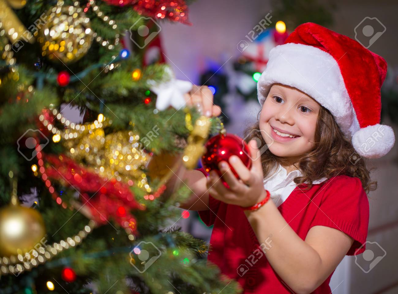 30b55e8b400da Little girl in Santa hat decorates a Christmas tree Stock Photo - 69532368