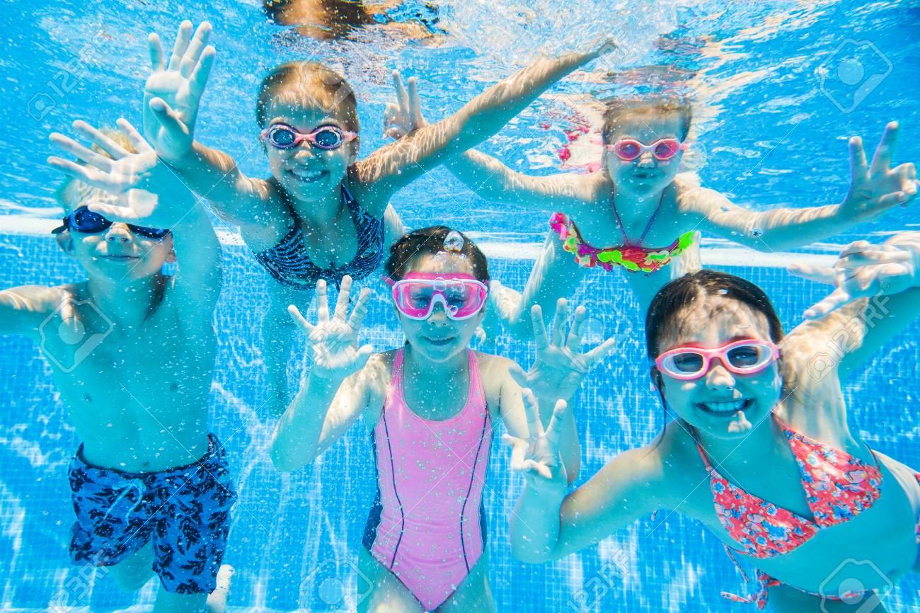 little kids swimming in pool underwater. - 82019199