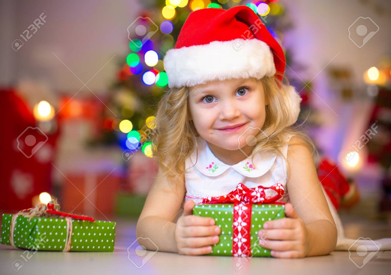 79e0351017af5 little girl in Santa hat holding a present under the Christmas tree Stock  Photo - 88916591