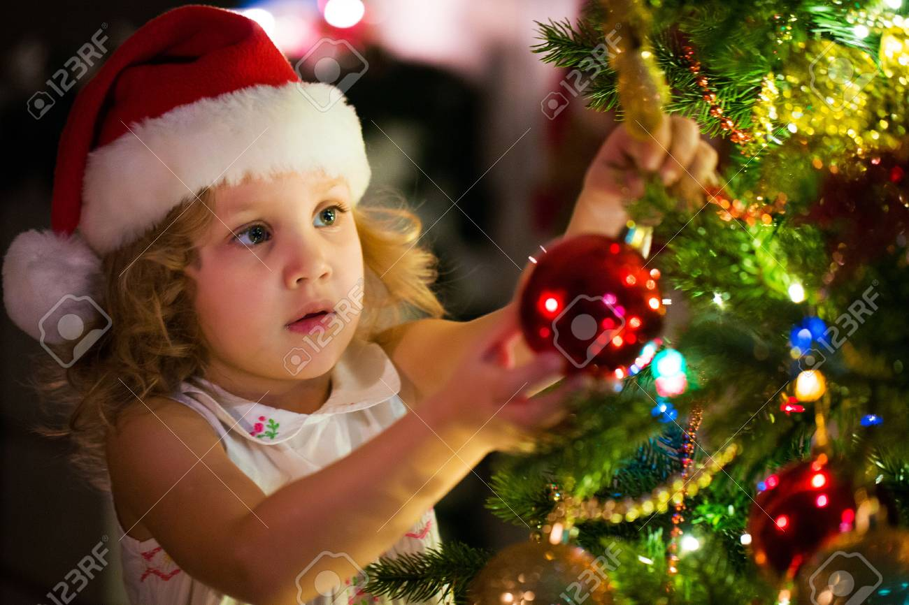 5bd57ef105898 Little girl in Santa hat decorates a Christmas tree Stock Photo - 91318374