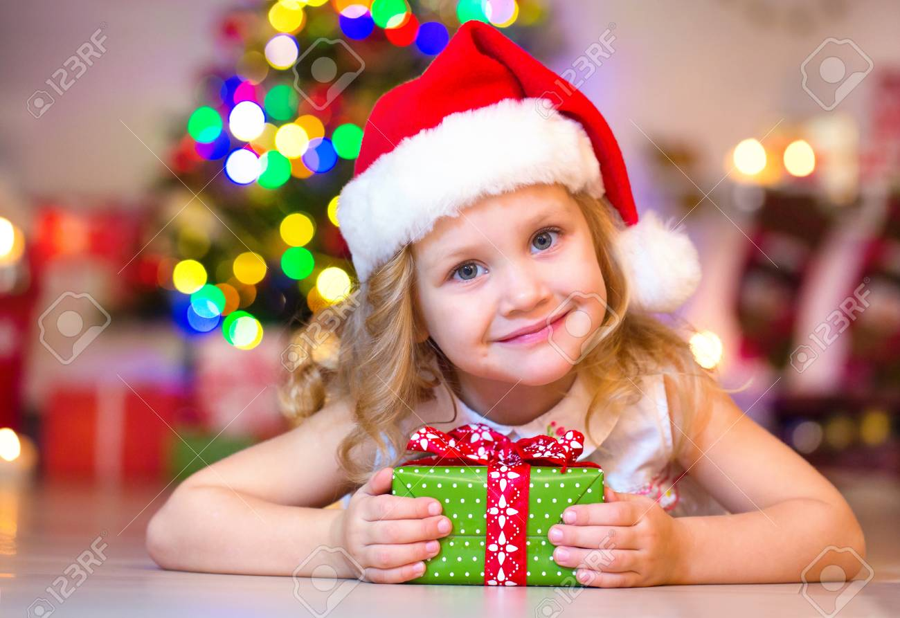 687a2ef9b1e53 little girl in Santa hat holding a present under the Christmas tree Stock  Photo - 91506625
